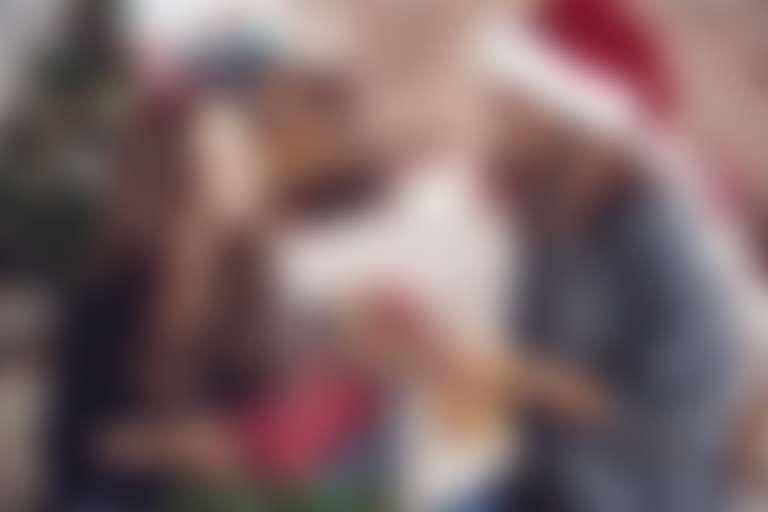 две девушки обмениваются новогодними подарками, на одной из них красный колпак, в глубине наряженная елка