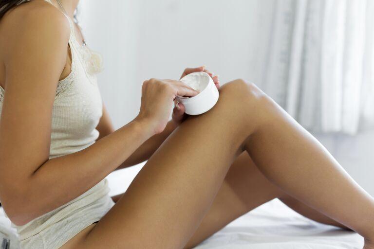 Девушка наносит на кожу ног смягчающий крем