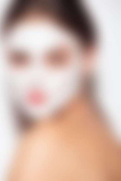 Брюнетка с очищающей маской на лице.