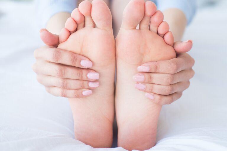 на белой постели пальцы с нежно-розовым маникюром держат ухоженные стопы