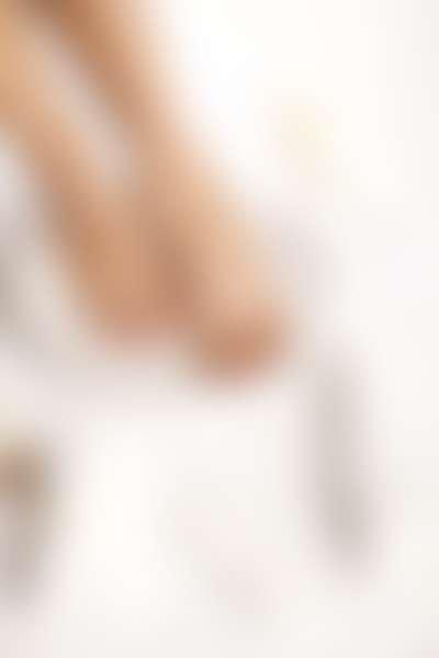 на белом фоне в белом тазике (ванночке для ног) в окружении белых аксессуаров мокрые стройные, ухоженные ноги