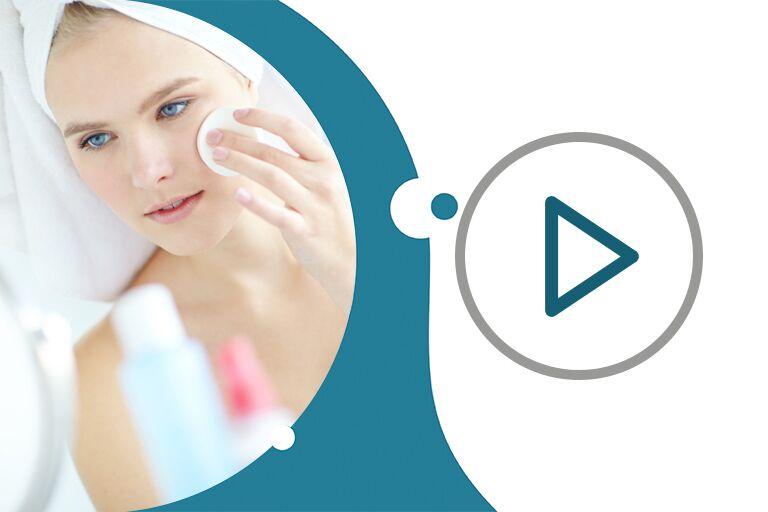 девушка с собранными в полотенце волосами перед зеркалом протирает лицо ватным диском с тоником