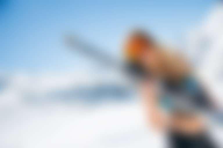 Девушка на фоне заснеженных гор держит в руках лыжи.
