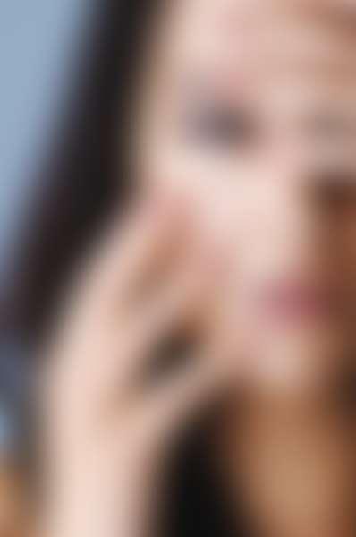Брюнетка с темными глазами держит руки у лица
