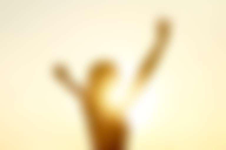 Девушка на закате стоит навстречу солнцу, силуэт с поднятыми руками