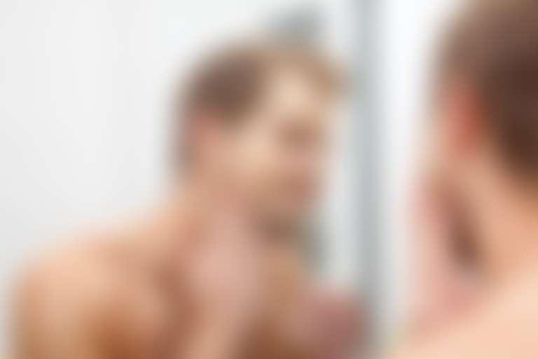 Мужчина наносит на кожу средство для роста бороды.