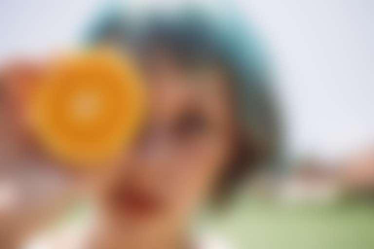 Девушка с веснушками на лице держит в руках апельсин