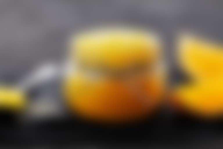 Тертый апельсин в стеклянной банке, рядом на столе апельсиновые дольки