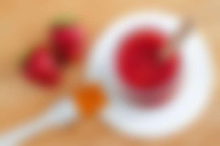 Измельченная клубника в стакане, рядом на столе лежат целые ягоды клубники