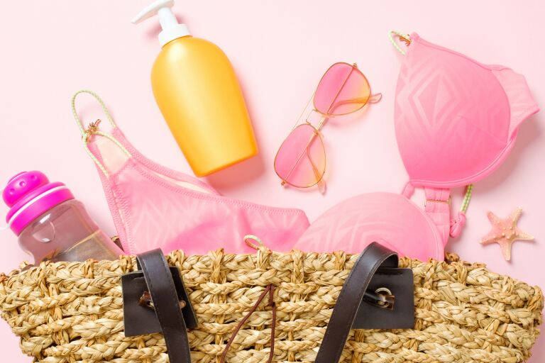 Соломенная сумка. а из нее выпадают розовая бутылка для воды, солнцезащитный крем, розовые очки, розовый бюстгальтер