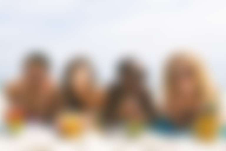 Четыре девушки с разным фототипом на пляже пьют коктейли