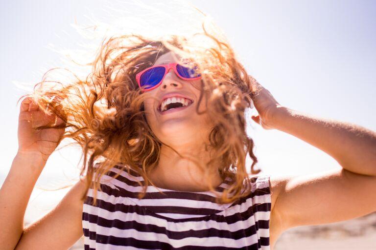 Девушка в розовых солнечных очках радуется солнцу