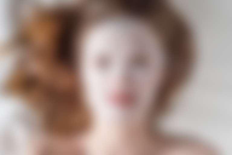 Девушка с тканевой маской на лице.