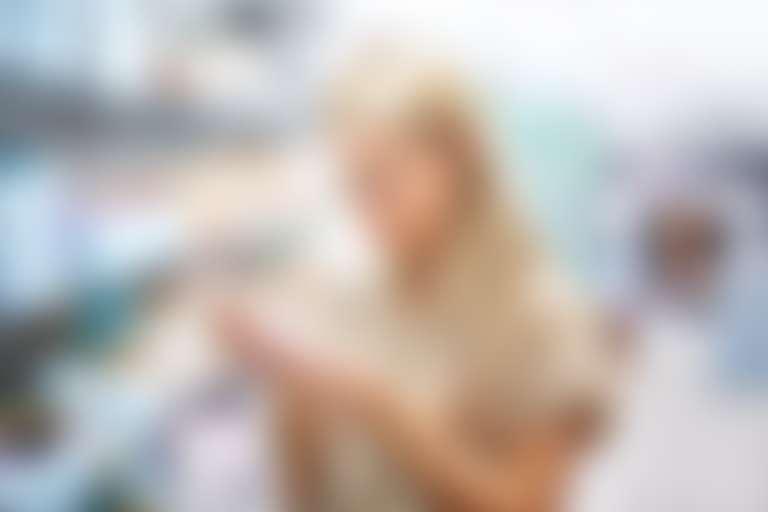 Девушка в косметическом отделе изучает упаковку средства