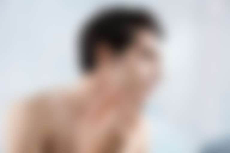 Парень рассматривает в зеркале лицо после бритья