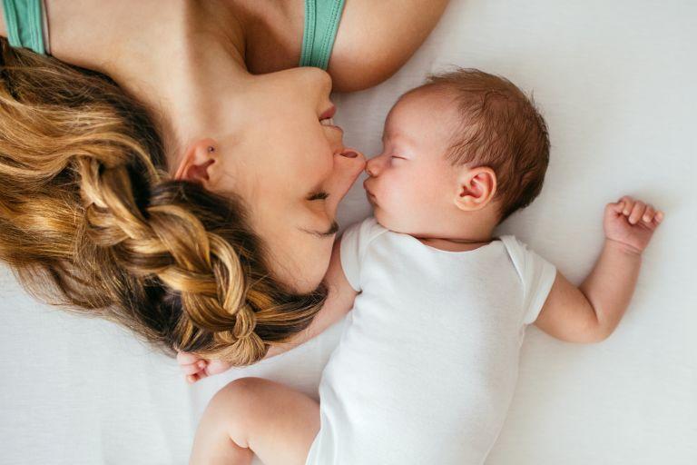Мама лежит с младенцем на кровати, вид сверху