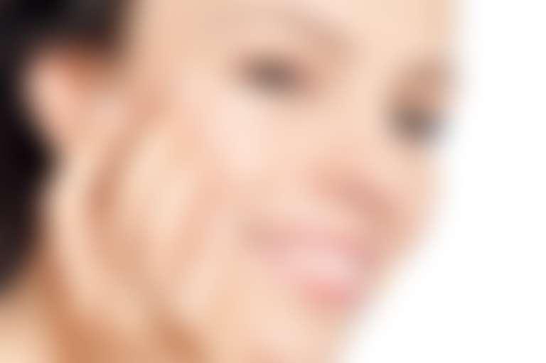 Девушка нанесла крем под глаза и улыбается.