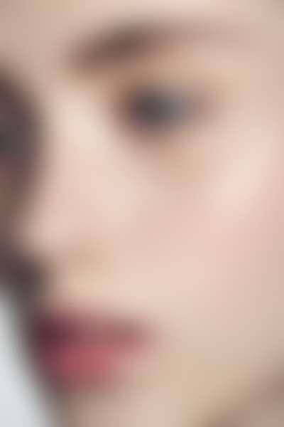 Крупным планом лицо с нанесенным кремом для области вокруг глаз.