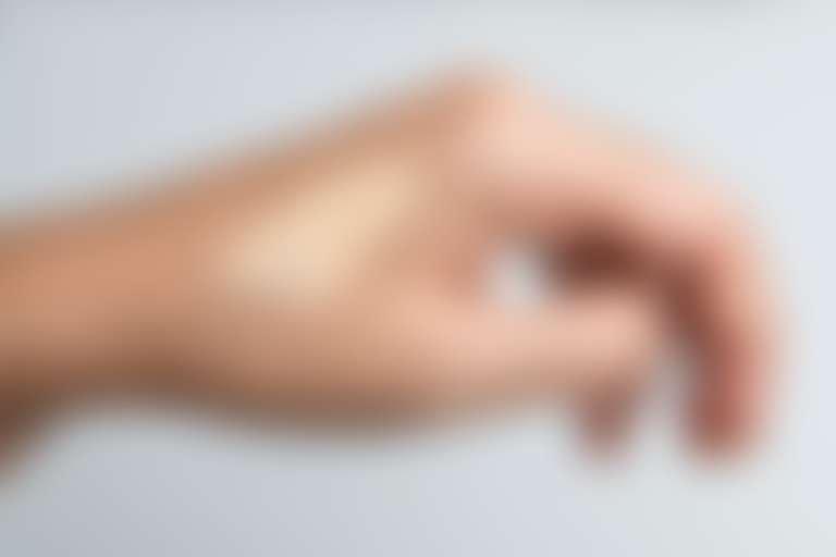 Крупно кисть руки, на которой девушка пробует текстуру BB-крема