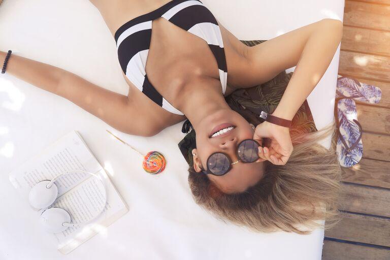 девушка лежит у бесценна в солнечных очках, загорает
