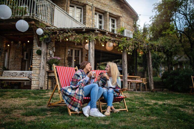 Две девушки сидят на лужайке перед домом