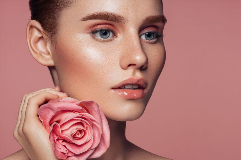 Девушка с идеально чистым лицом и символом Lancome – розой в руках