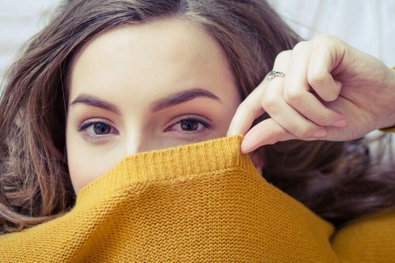 Девушка закрывает лицо свитером