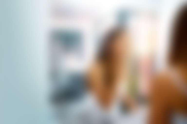 Отражение в зеркале девушки с длинными волосами, прикасающейся к лицу
