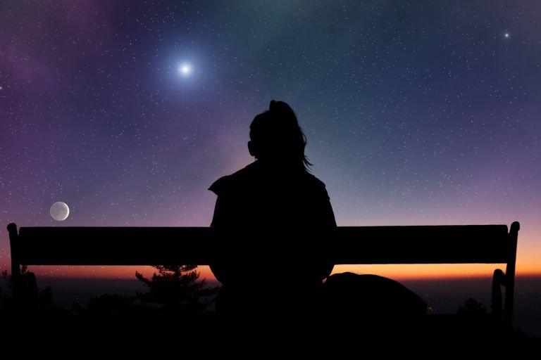 Силуэт девушки со спины на фоне ночного неба