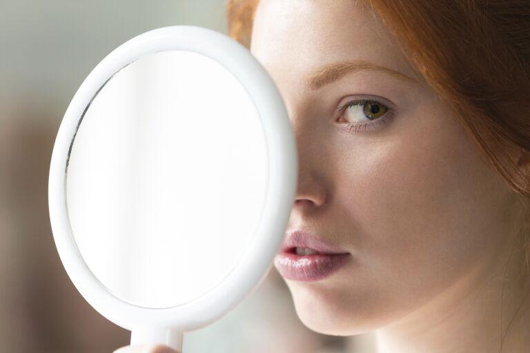 Рыжая девушка с круглым ручным зеркалом