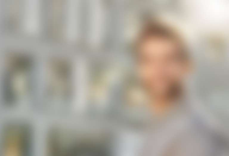 Молодой человек с бородой стоит напротив офисного здания