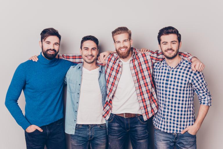 У стены стоят четверо мужчин с разными по длине и форме бородами.