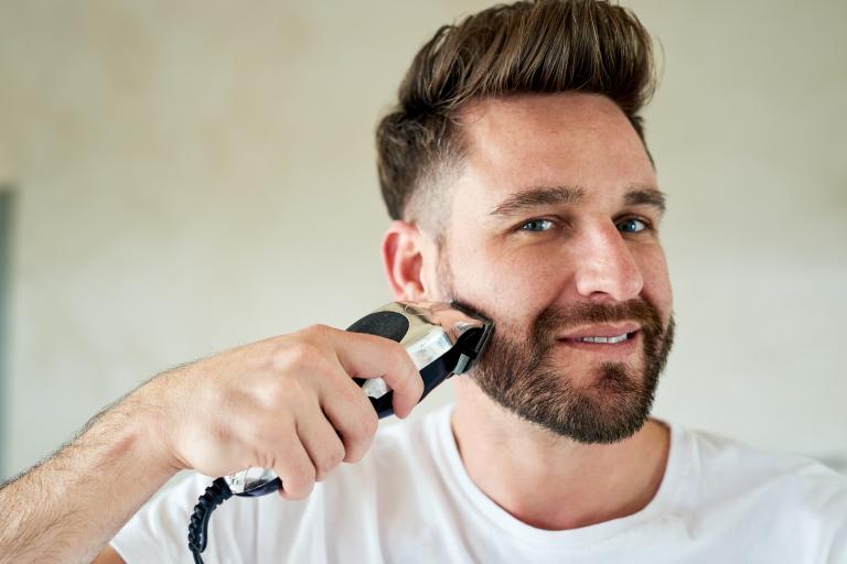 Мужчина подбривает бороду с помощью триммера.