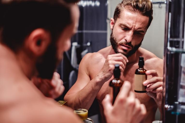 Мужчина перед зеркалом умасливает бороду маслом
