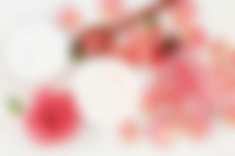 На столе разложены роза, розовые лепестки, баночка с кремом, деревянная ложка, розовое масло в бутылке.