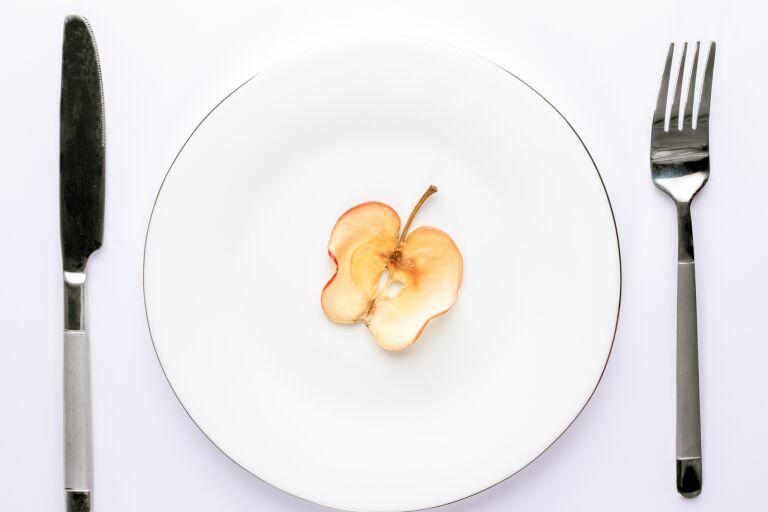 тонкий сухой срез яблока на белой тарелке на белой скатерти с ножом и вилкой