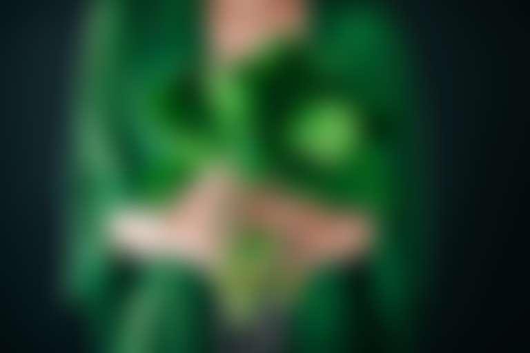 листовые овощи держит девушка с ухоженными руками и в зеленой одежде