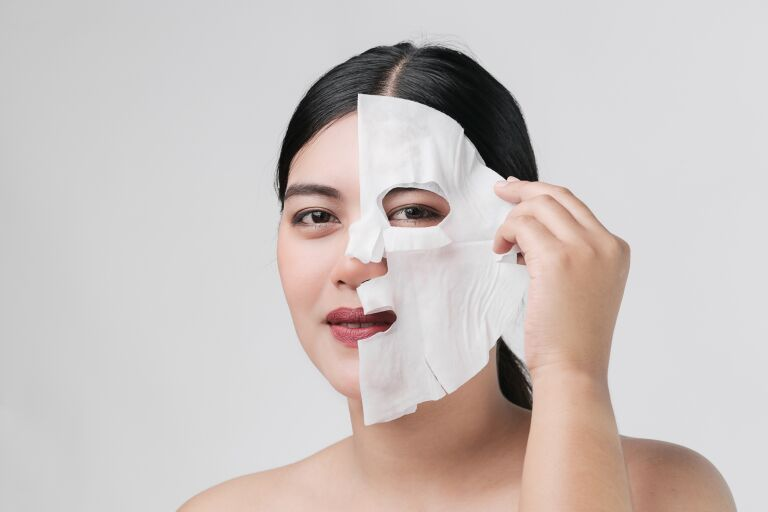 Брюнетка снимает с лица тканевую маску