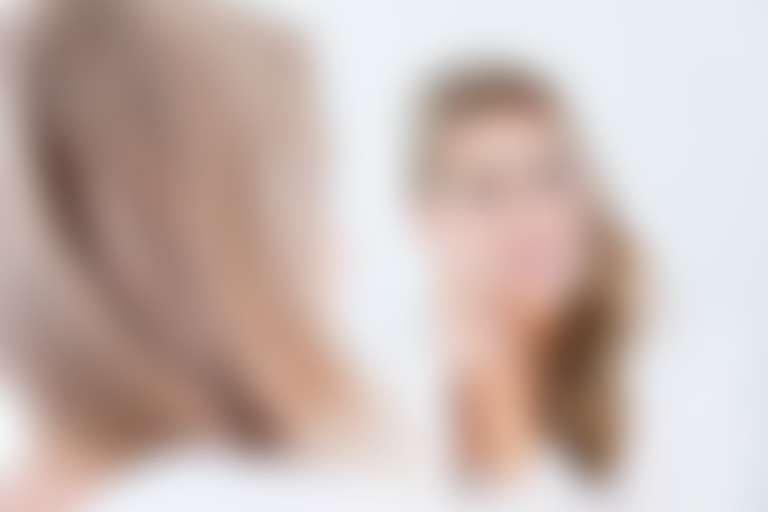Отражение в зеркале девушки, протирающей лицо ватным диском.