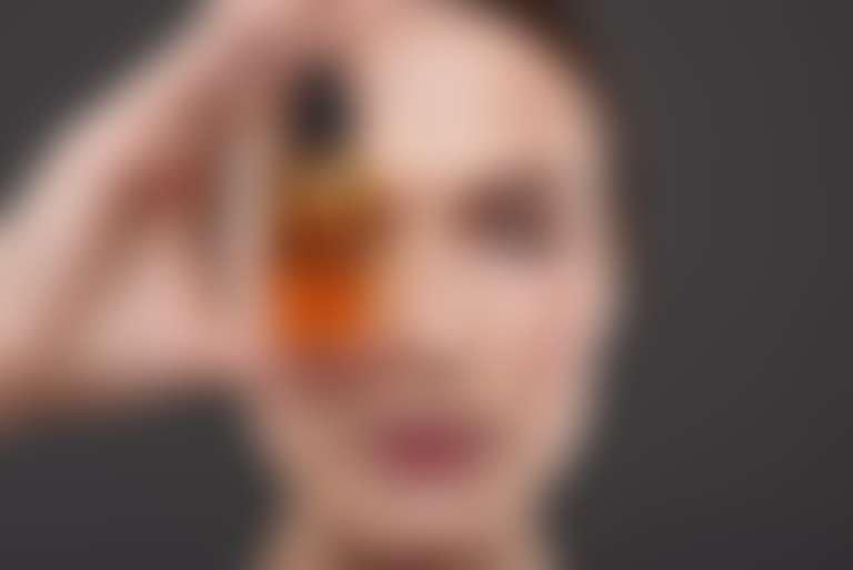 Девушка держит у глаза стеклянный флакон с оранжевой жидкостью