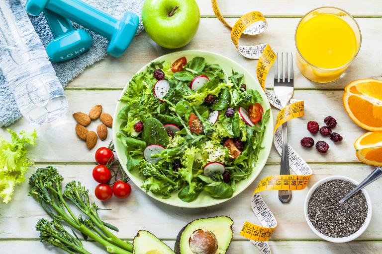На столе тарелка с овощами, кино, авокадо, апельсином