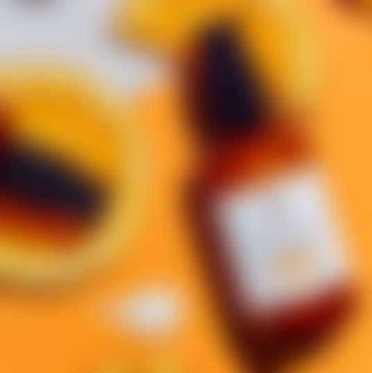 Концентрат с витамином С от Kiehl's на фоне разрезанных апельсинов