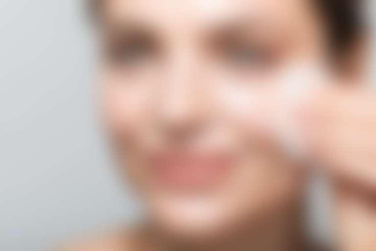 Крупный план лица улыбающейся девушки, протирающей лицо ватным диском.