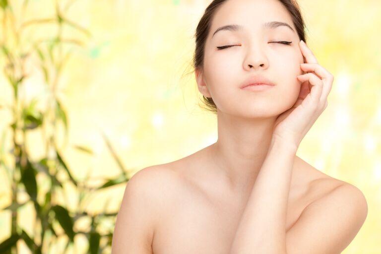 Красивая корейская девушка с закрытыми глазами приложила пальцы одной руки к щеке