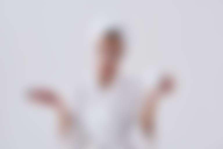 Девушка в белом халате и с тюрбаном из полотенца на голове в патчах разводит руками