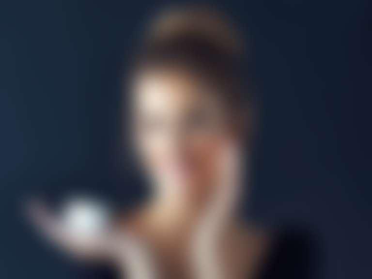 Улыбающаяся девушка держит в руке банку с кремом