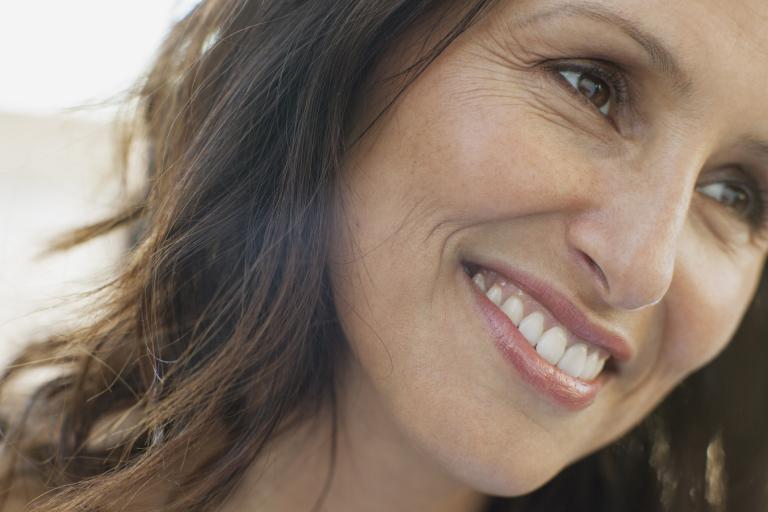 темноволосая женщина улыбается, видны морщинки около глаз и рта