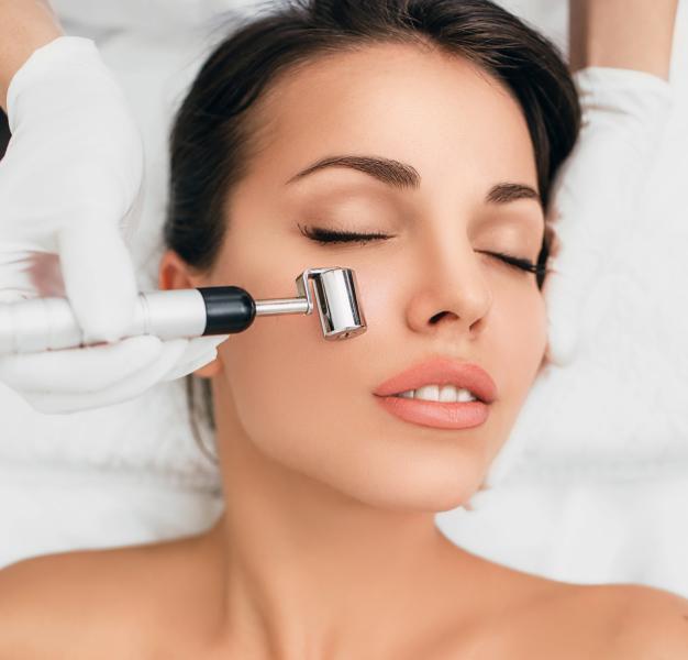 темноволосая девушка с ухоженной кожей лежит с закрытыми глазами по лицу косметолог в белых перчатках проводит массажером
