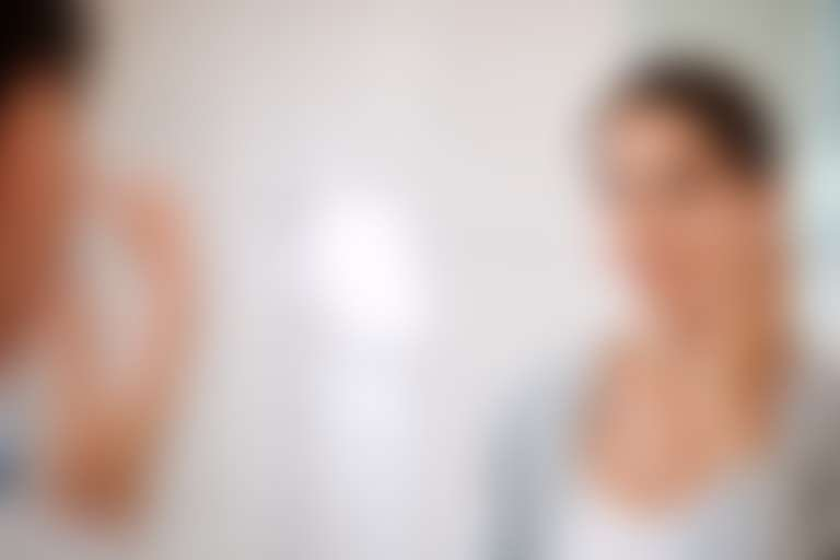 темноволосая девушка перед зеркалом наносит на скулу белый крем