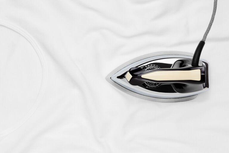 Утюг на белой ткани